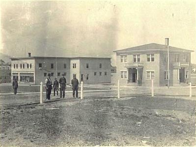 Workers installing a fence around the school yard (1912).