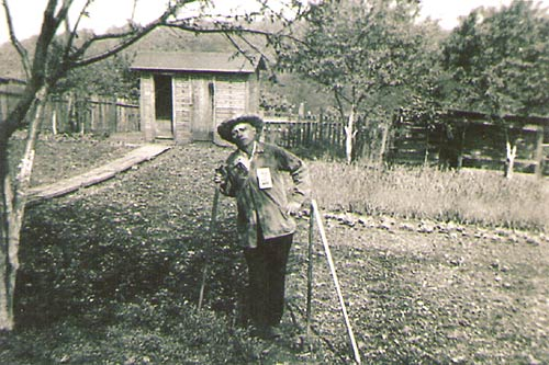 Photo of Frank Arello, working in his backyard garden on 3rd Street (circa 1939). Note the wooden sidewalk leading to the outhouse/coal house in the back.