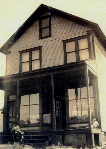 """The town Barber Shop showing a sign in the front window reading """"Sanitary Barber Shop"""" (circa 1920) . In the second floor window (second from the right) there is a banner for the Red Men of Heilwood."""