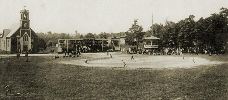 "Heilwood baseball game, circa 1920. L to R: the Catholic Church, the grandstand, ""The Green"" (houses), the band stand, and on the far right - Heilwood Park"