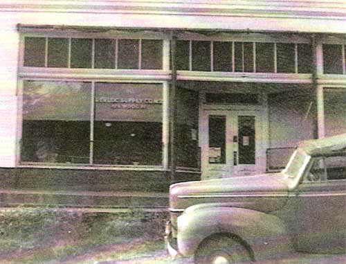 "Photo showing the name of the next-to-last owner of the store, circa 1942. The name painted on the window to the left of the front doors reads ""Revloc Supply Company - Heilwood, Pa."""