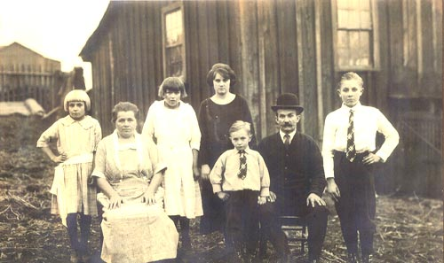An Eastern European family in front of a board-and-batten style Heilwood shanty.