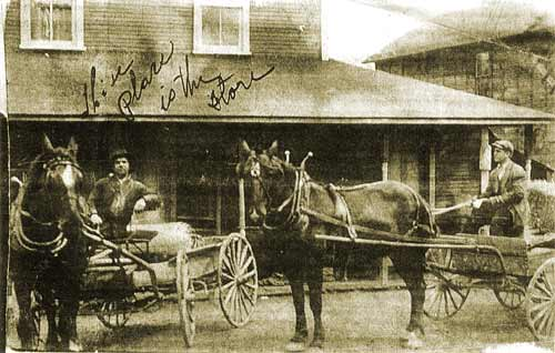 "A photo taken in Jewtown, with Andy Seaman on the right and Harry ""Columbus"" Eskovitz on the left. Seaman's Store is in the background, with both men seated on delivery wagons."