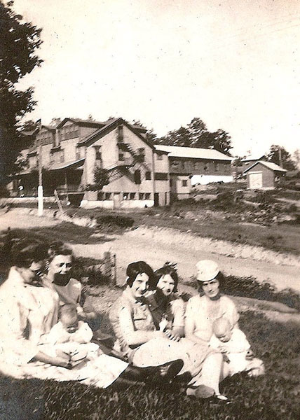 Photo showing a group of women with the Heilwood Inn in the background. To the right of the Inn is a vacant lot where the Meat Market/Butcher Shop used to sit, before it was destroyed in a 1924 fire.