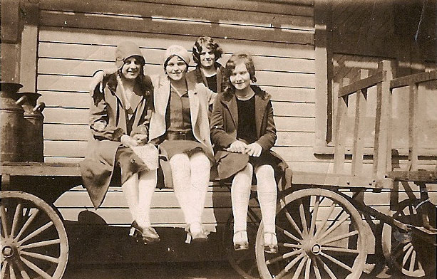 Four women sitting on a cart outside the Heilwood Railroad Station (ca. 1930s)